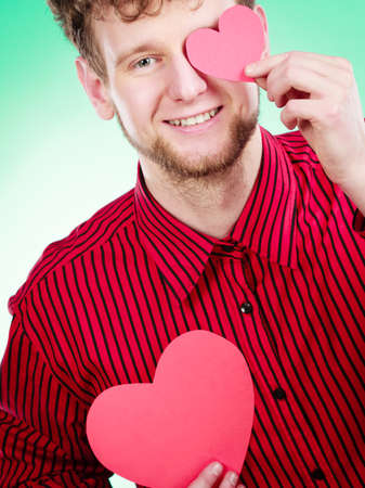 Love and help from people. Charming lovely man with two red paper hearts persuade to be good helpful hopeful. Valentines Day or charity concept. Stock Photo