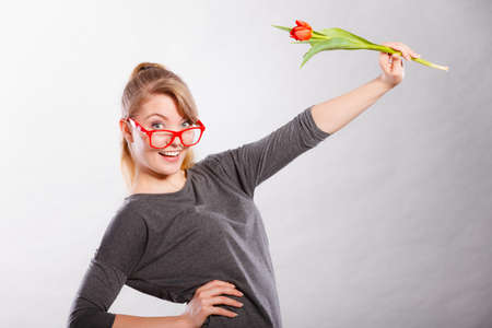 Spring time. Craziness and fun concept. Playful happy girl playing with flower. Joyful smiling funny positive female person making crazy figures with tulip. Stock Photo