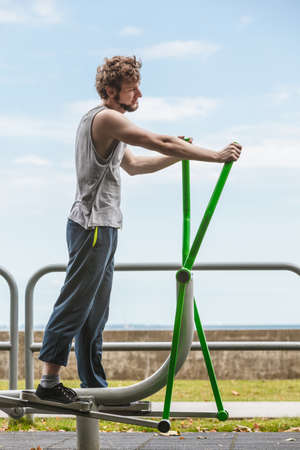 eliptica: Active young man exercising on elliptical trainer machine. Muscular sporty guy in training suit working out at outdoor gym. Sport fitness and healthy lifestyle concept.