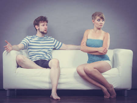 Bad relationship concept. Man and woman in disagreement. Young couple sitting on couch at home having quarrel, offended wife and unhappy husband Stock Photo