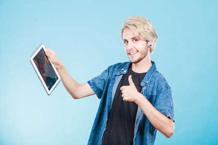Education social media. Modern technology internet concept. Stylish handsome young guy using tablet computer, on blue color Stock Photo