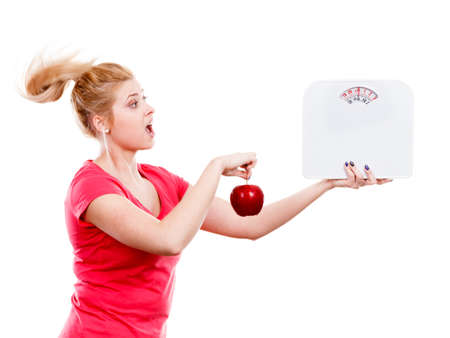 Healthy fit lifestyle, getting ready for diet concept. Happy sporty woman holding red apple and weight machine.