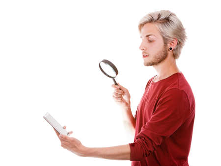 Funny young guy reading message on smart phone looking with ssurprised face expression, using loupe magnifying glass, isolated on white Stock Photo