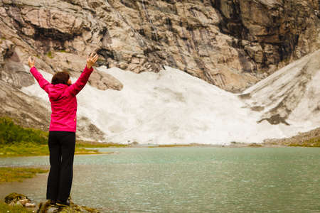 Travel concept. Happy free tourist woman in happiness and elated enjoyment with arms raised outstretched up looking at mountains in Norway Stock Photo