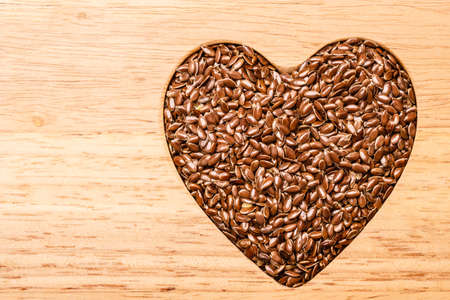 linum: Diet healthcare healthy food. Raw flax seeds linseed heart shaped on wooden board background. Stock Photo