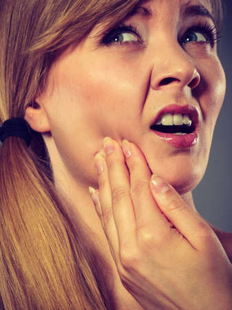 Dental care and toothache. Young woman achy girl suffering from terrible tooth pain, touching pressing her cheek by hand palm closeup