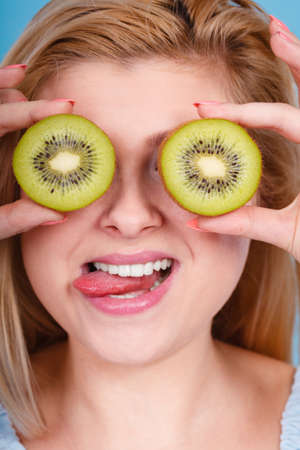 pretending: Healthy diet, refreshing food full of vitamins. Woman holding sweet delicious green kiwi fruit, pretending it is eyeglasses. Stock Photo