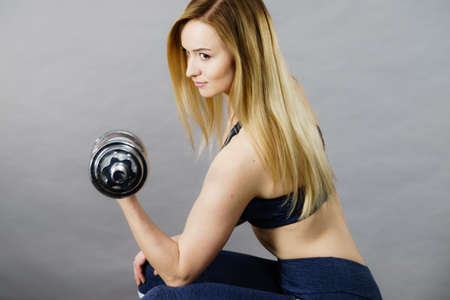 gaining: Strong woman lifting dumbbells weights. Fit girl attractive blonde model exercising gaining building muscles. Fitness and bodybuilding, on grey