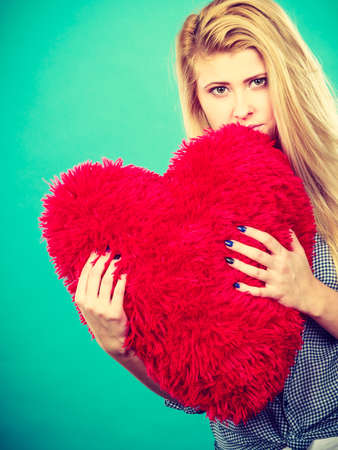 sad heart: Break up, divorce, bad relationship concept. Sad, depressed woman holding big red fluffy pillow in heart shape, she needs love.