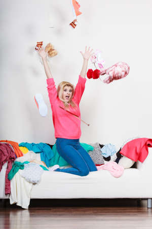 messy clothes: Clothing dilemmas concept. Shocked woman sitting on messy couch throwing clothes above head. Stock Photo