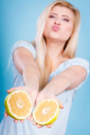 Woman smiling girl holding two halfs of yellow grapefruit citrus fruit in hands, on blue. Healthy food, dieting concept. Stock Photo