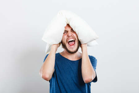 Stressful unpleasant situation conflict. Angry mad young man closing ears with pillow, protecting from loud noise. Guy not wanting to listen or can not fall asleep Stock Photo