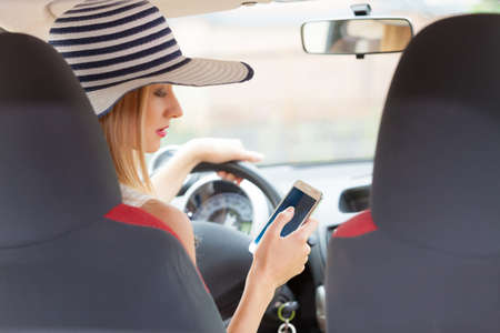 Distracted driver. Young attractive woman using mobile phone, texting or read message while driving the car.