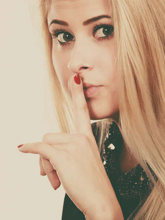 rumour: Gestures and signs concept. Attractive blonde woman making silence gesture with finger close to her mouth.