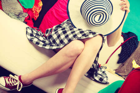 messy clothes: Fashion, clothing, accessories concept. Woman sitting on sofa in mess wearing checked dress and sneakers holding sun hat.