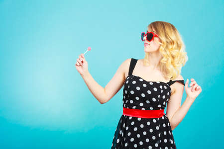 Woman attractive cheerful blonde girl holding little lollipop candy in hand. Sweet food and enjoying concept. Studio shot blue