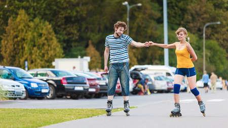 Vacaciones, personas activas y concepto de amistad. Young fit couple on patines de ruedas al aire libre, mujer y hombre patinar juntos en la calle de la ciudad