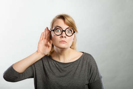 Rumors and gossips concept. Newsmonger girl making listening gesture. Shocked surprised gossiping woman. Gossip and chatter. Stock Photo
