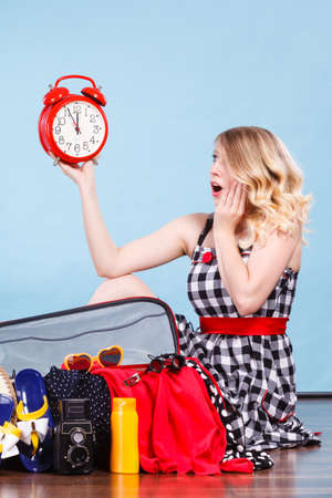 Time for travel, being late concept. Terryfied woman sitting on floor with messy packed suitcase holding big red old clock