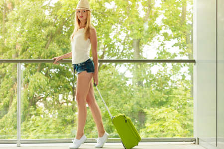 Travel, adventure, teenage journey concept. Attracitve woman wearing denim shorts, white top and sneakers walking with green suitcase going to terminal Stock Photo