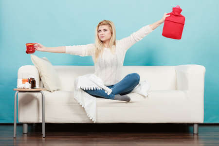 Woman having flu showing ideas how to deal with cold, holding hot water bottle and tea in cup sitting on sofa Stock Photo
