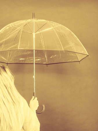 Blonde woman wearing raincoat holding transparent umbrella checking weather if it is raining. Back view, sepia colors