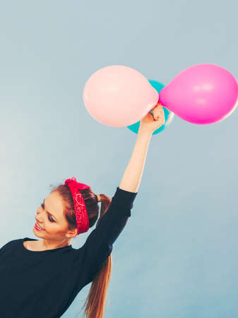 hankie: Joy fun and freedom concept. Blonde smiling woman with colorful latex balloons flying balls. Retro fashion styled girl portrait. Stock Photo