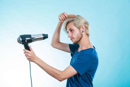 Stijl en mode. Jonge trendy mannelijke hairstylist kapper met een nieuw idee van uiterlijk veranderen. Blonde man met een haardroger en kam het creëren van nieuwe kapsel, op blauw