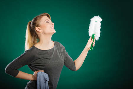 doing chores: Household duties concept. Young energy girl playing with cleaning cloth doing domestic chores. Cheerful playful housewife ready to clean house. Stock Photo
