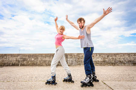 roller: Active young people friends in training suit rollerskating outdoor. Happy woman and man with hands up.