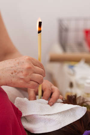 Terapist doing ear candling, Alternative therapy session, natural medicine, health care. Stok Fotoğraf