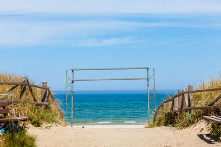 blue waters: Metal entrance to beach, calm blue sea waters in background. Sunny weather.