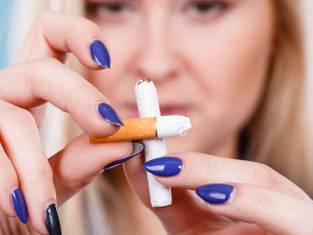 rid: New Year resolutions, bad habits, unhealthy lifestyle concept. Woman breaking cigarette, getting rid of addiction
