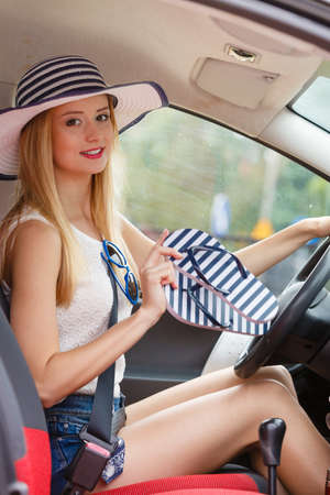 Summer road trip, travel concept. Pretty woman sit in car holds flip flops in hand, ready for the journey on holidays