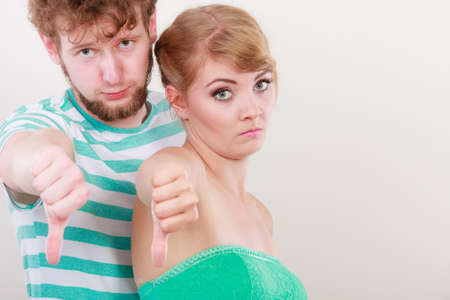 disapprove: Couple doing bad sign showing thumbs up hand gesture Stock Photo