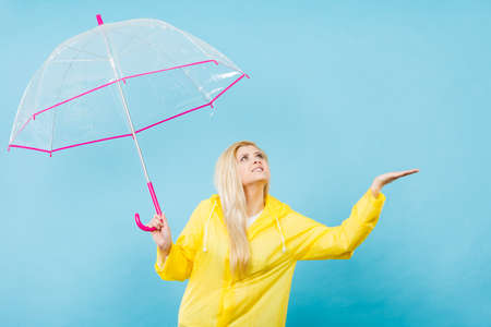 Blonde woman wearing yellow raincoat holding transparent umbrella checking weather if it is raining.