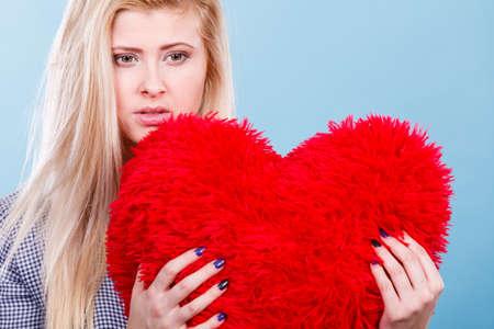 Break up, divorce, bad relationship concept. Sad, depressed woman holding big red fluffy pillow in heart shape, she needs love.