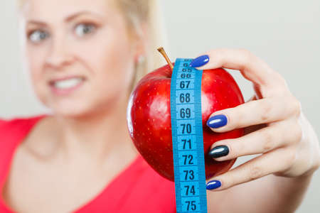 Healthy fit lifestyle, getting ready for diet concept. Happy sporty woman holding red apple and measuring tape. Stock Photo