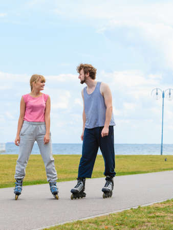 Active holidays, exercises, relationship concept. Woman and man wearing rollerskates standing and looking at each other