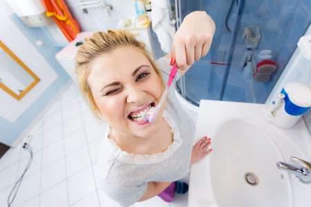 whiten: Woman brushing cleaning teeth closeup. Funny blonde girl with toothbrush in bathroom. Oral hygiene. Unusual wide angle view