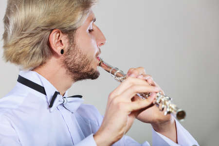 professional flute: Flute music playing professional male flutist musician performer. Young elegant stylish man with instrument