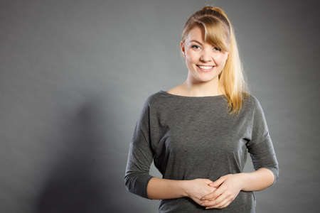 Charm and gladness. Blonde lovely girl in grey smiling. Happy glad charming female portrait.