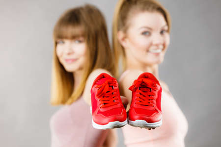 Two happy sporty smiling women presenting sportswear trainers red shoes, comfortable footwear perfect for workout and training.