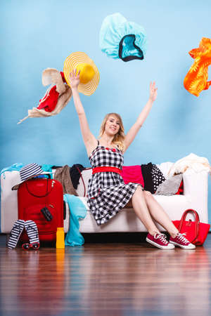Cleaning in the closet, packing for travel, fashion, happiness concept. Woman sitting on sofa throwing up lot of clothes. Clothing flying all over the place Editorial