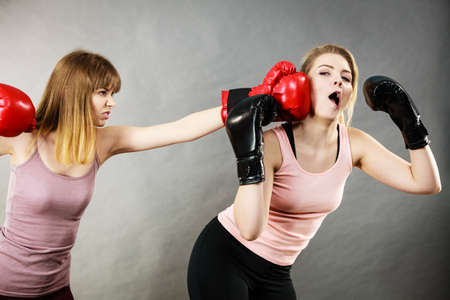 hostile: Agressive women having argue fight wearing boxing gloves, female friend being scared. Violance concept. Stock Photo