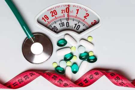 Healthy eating, medicine, health care, food supplements and weight loss concept. Pills with measuring tape and stethoscope on white scales