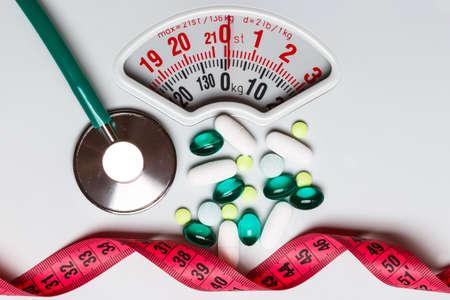 Mangiare sano, la medicina, l'assistenza sanitaria, integratori alimentari e il concetto di perdita di peso. Pillole con nastro di misura e stetoscopio su scale bianche Archivio Fotografico - 81623450