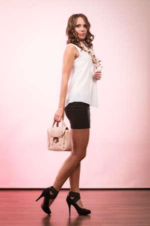 Elegant outfit. Female fashion. Girl in full length fashionable clothes high heels holding bag handbag. Stock Photo