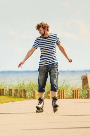 Holidays, active lifestyle freedom concept. Young fit man on roller skates riding outdoors on sea coast, guy rollerblading on sunny day