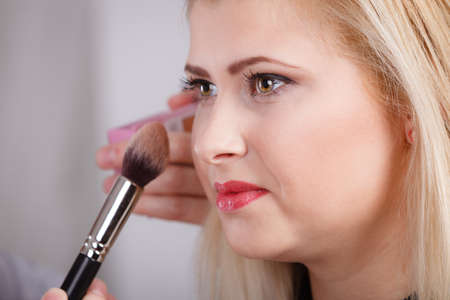 Visage, beauty of feminity concept. Happy woman getting her makeup done with professional brush